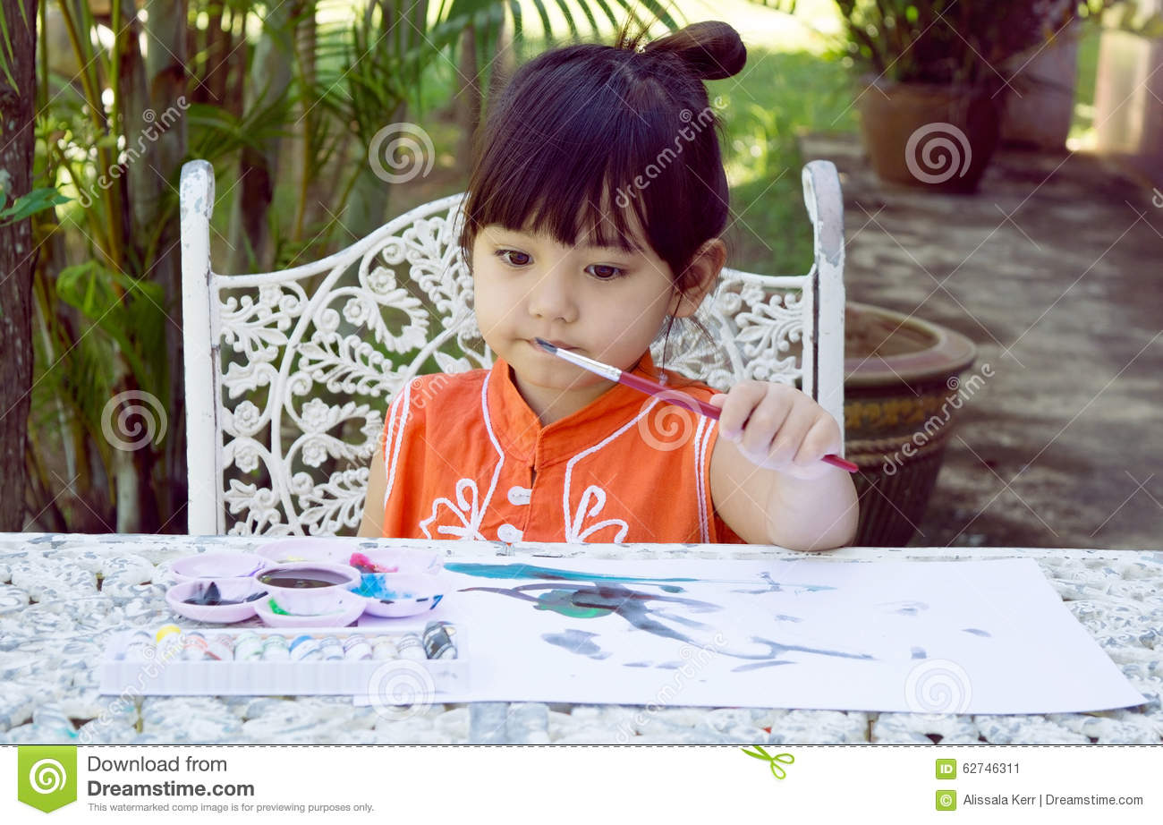 Little girl painting with paintbrush and water colors