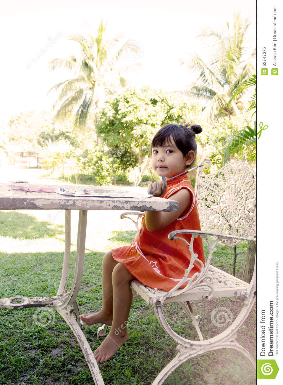 A little girl painting water colors on a table at home garden