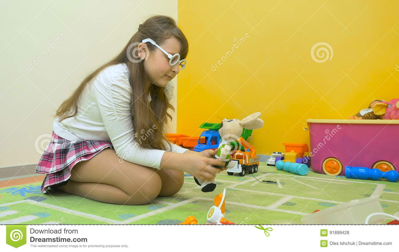Little girl playing doctor with toys in the room