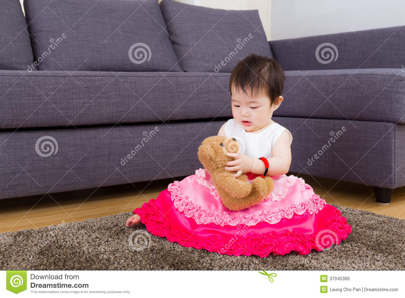 Little girl playing doll and sitting on carpet
