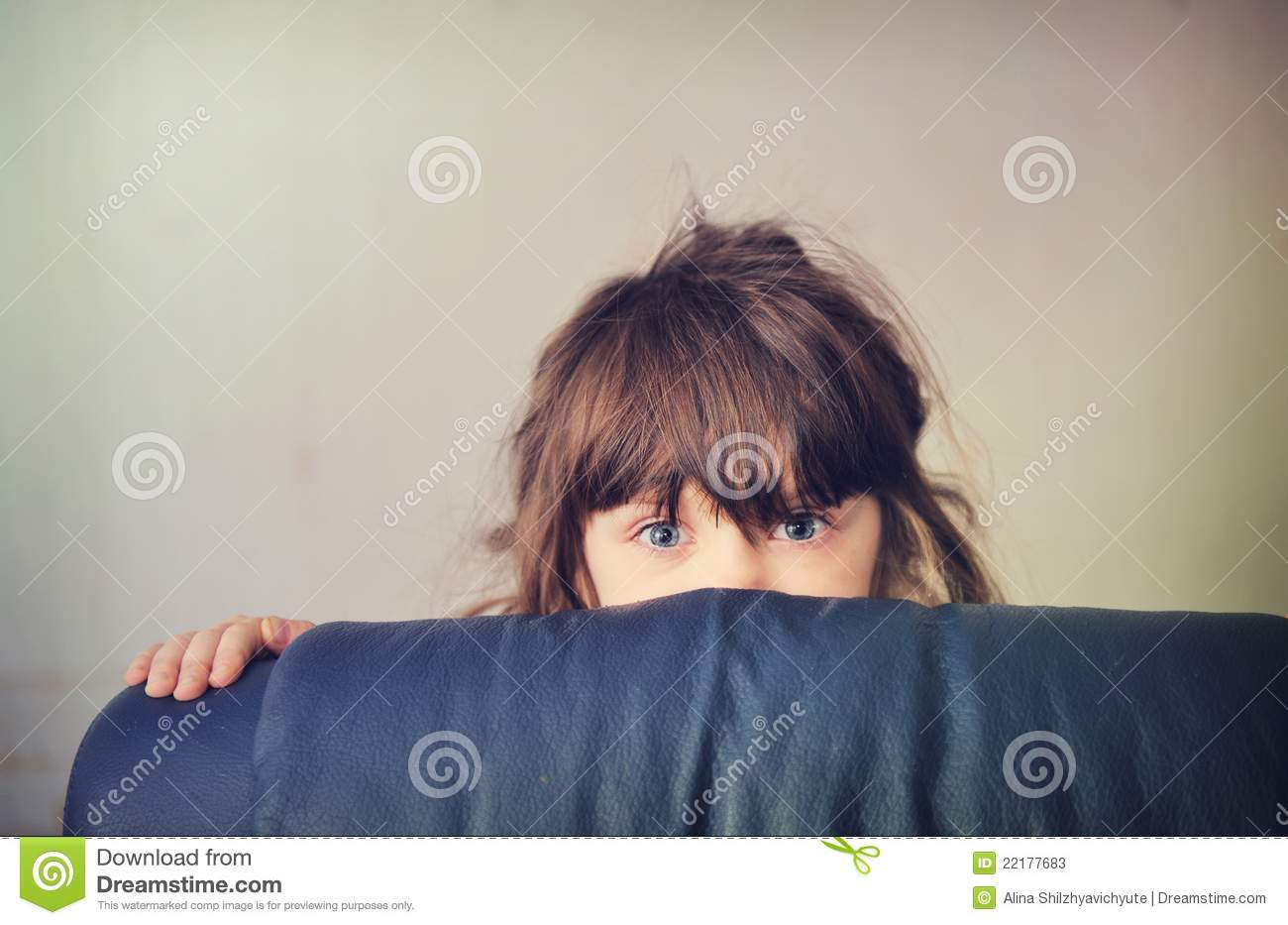 Little Girl Playing Hide And Seek Behind The Sofa Stock