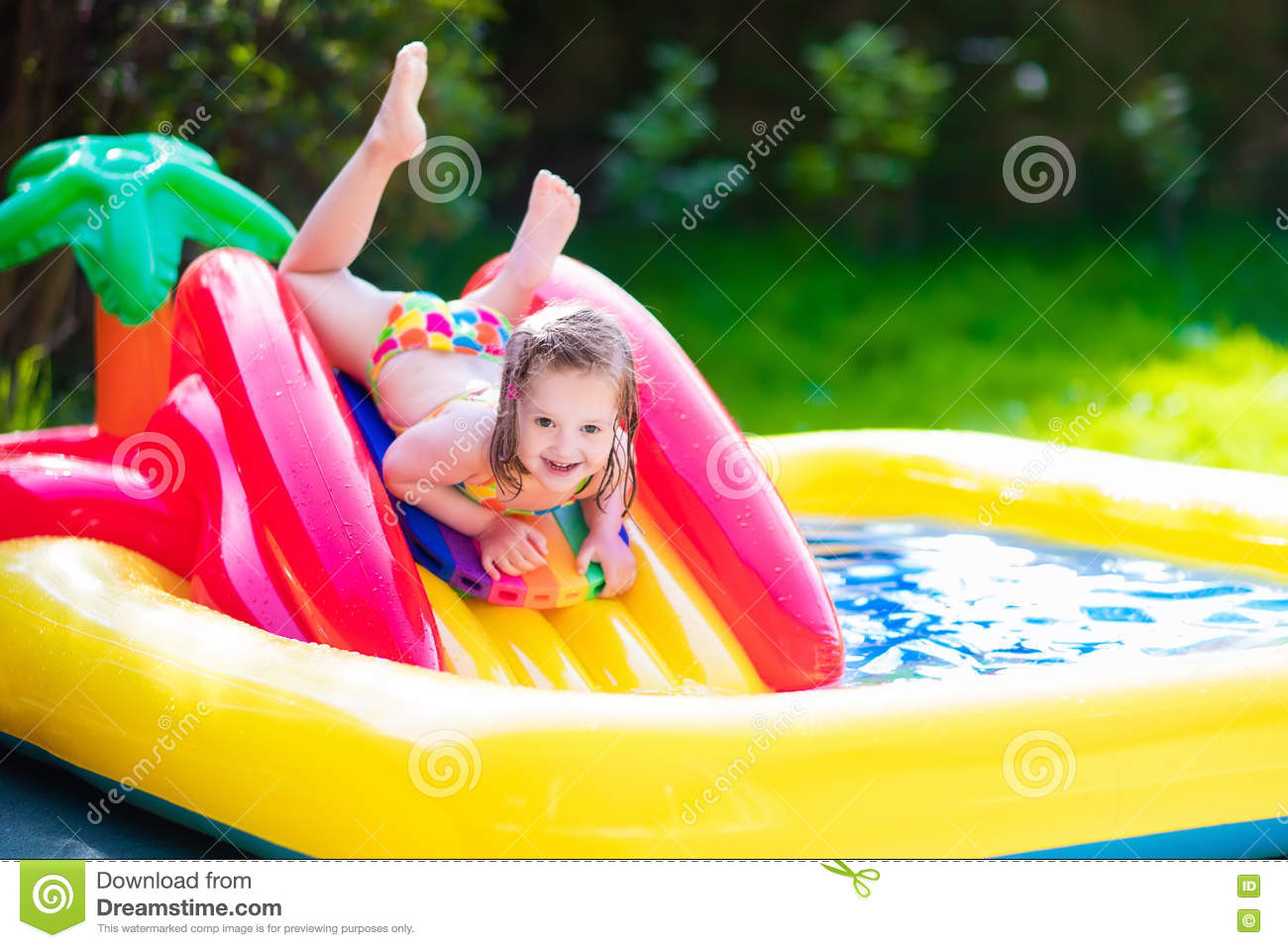 Little Girl Playing In Inflatable Garden Swimming Pool ...
