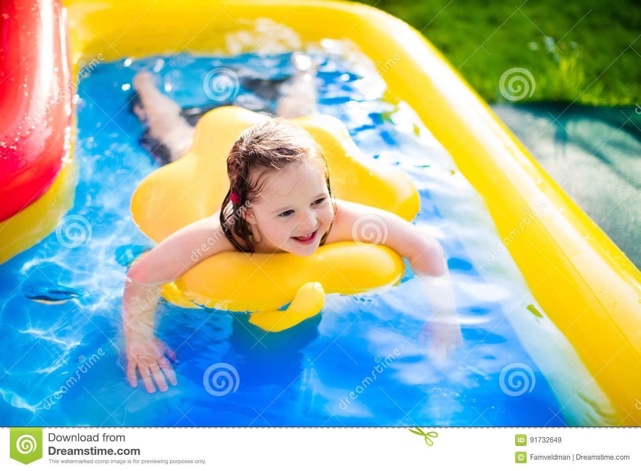 Little girl playing in inflatable garden swimming pool for Kids swimming pool