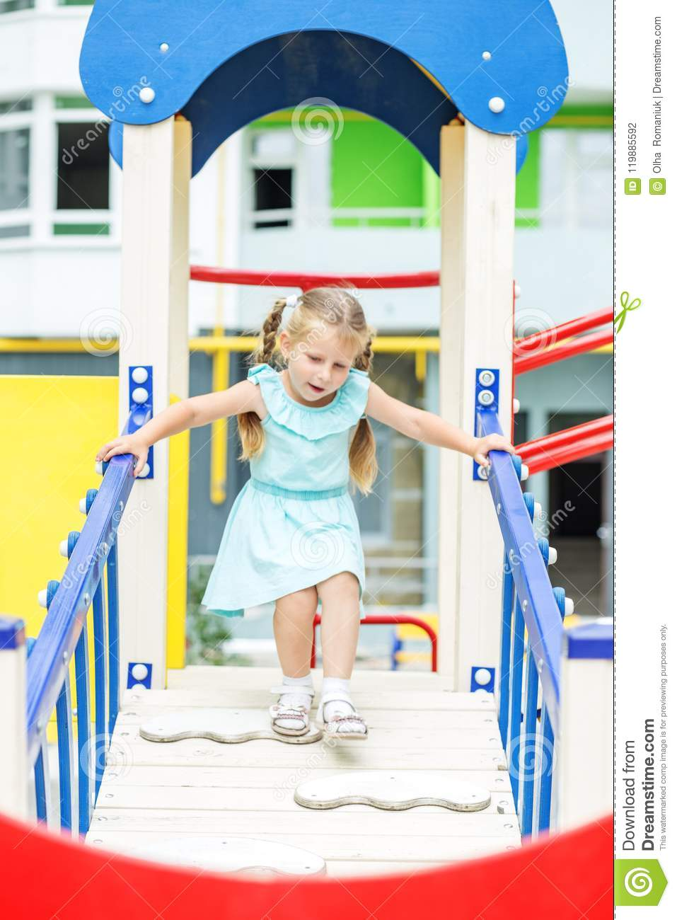 Little girl is playing on the playground. The concept of childhood, lifestyle, upbringing, kindergarten.