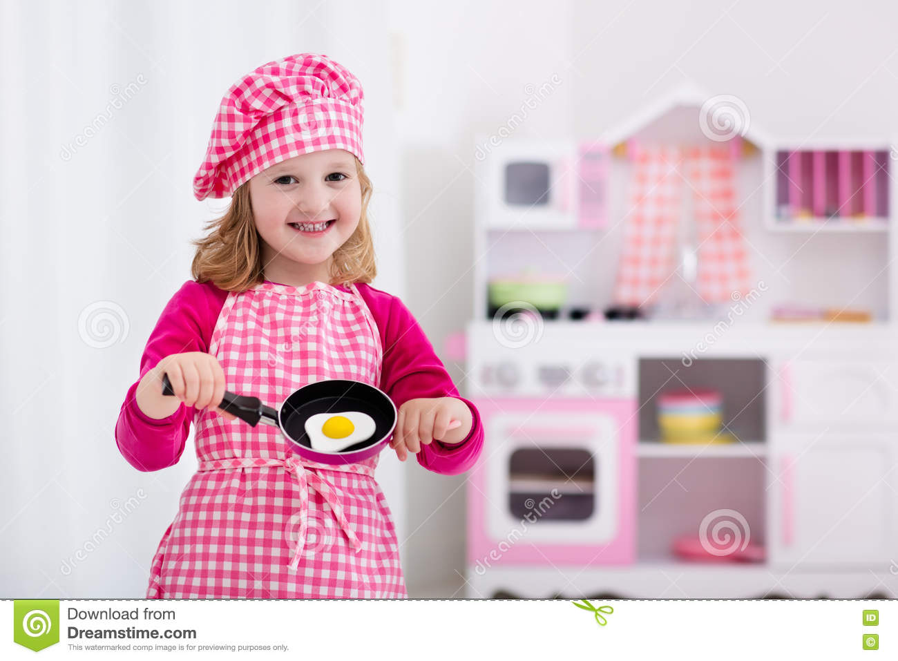 Little Girl Toys : Little girl playing with toy kitchen stock image