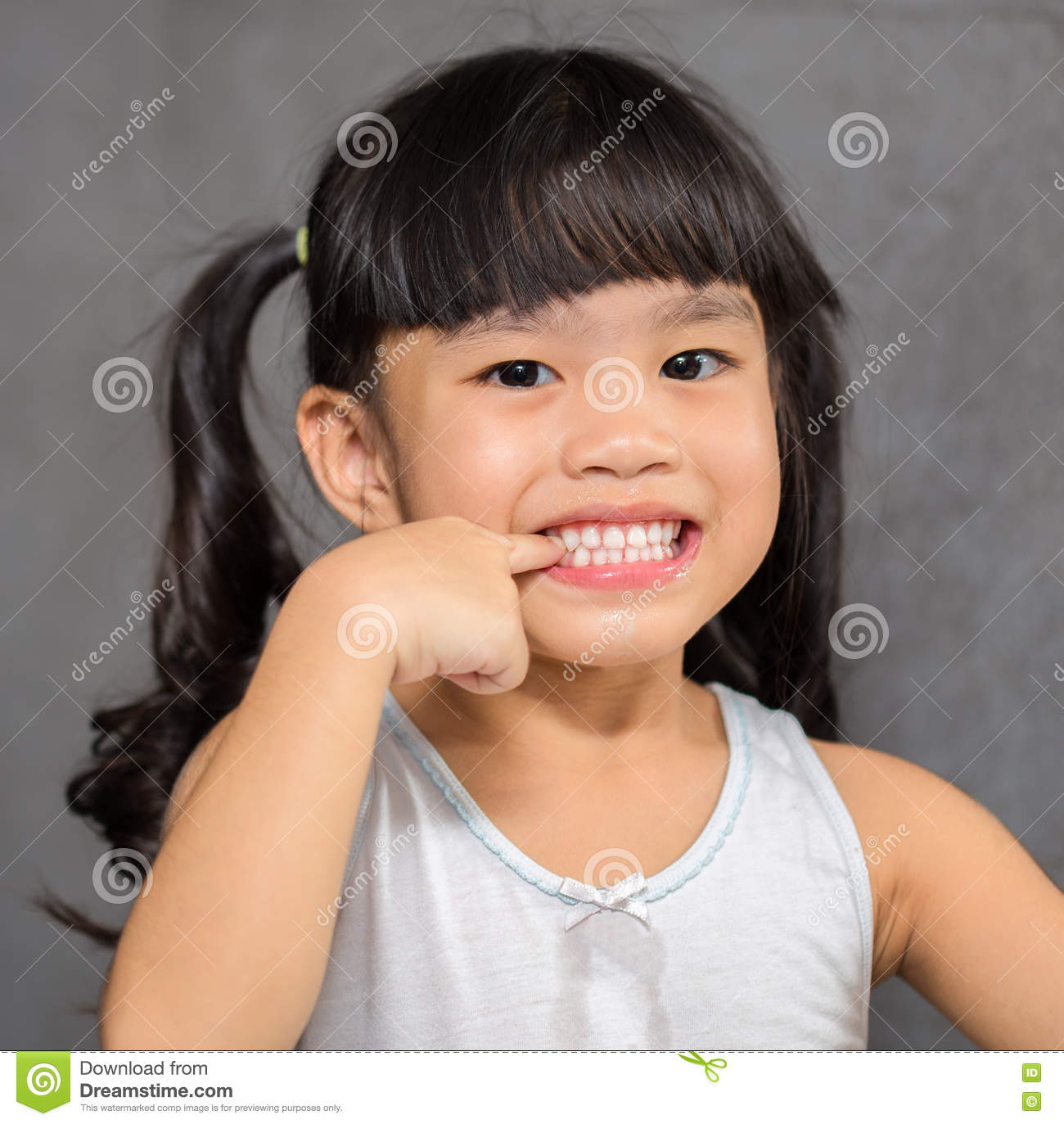 Little girl pointing teeth on white After brushing teeth feeling happy