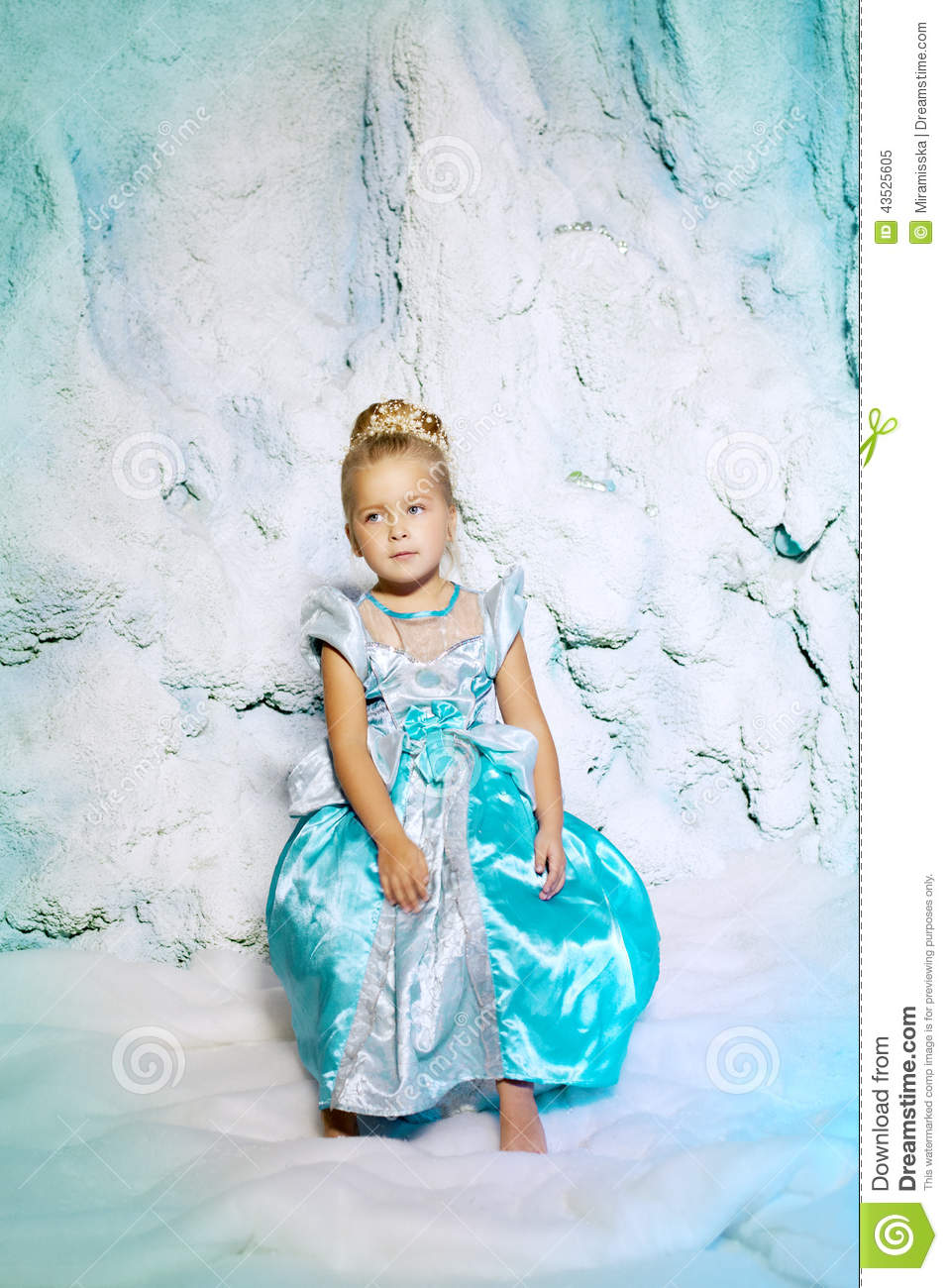 Little girl in princess dress on a background of a winter fairy tale baby snow queen sweet smiling child snowy kingdom kid in in carnival costume