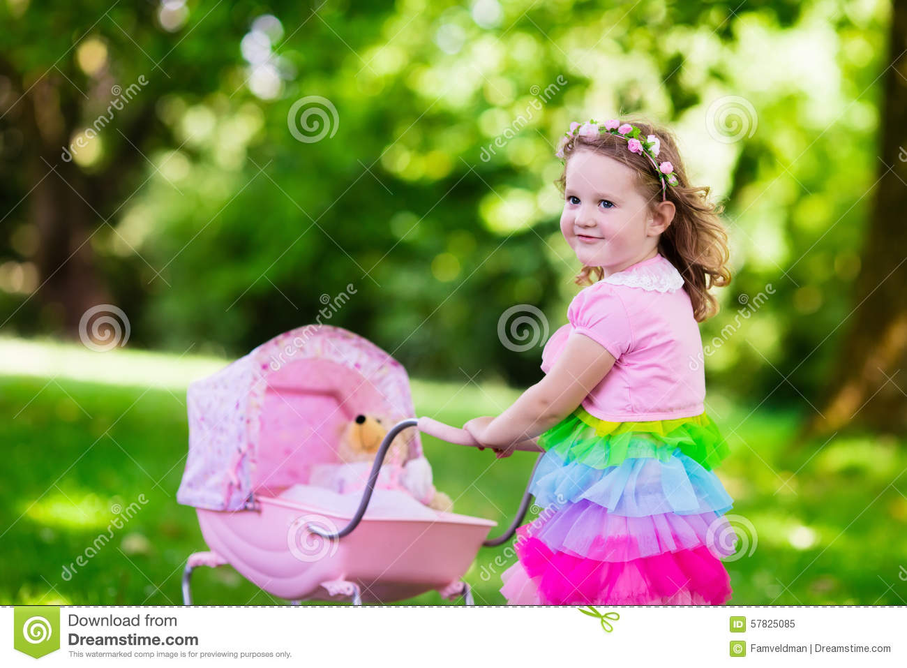 Little Girl Pushing A Toy Stroller Wth Doll Stock Photo