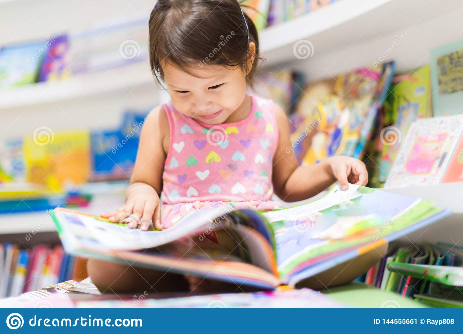 Little girl reading a book. Education
