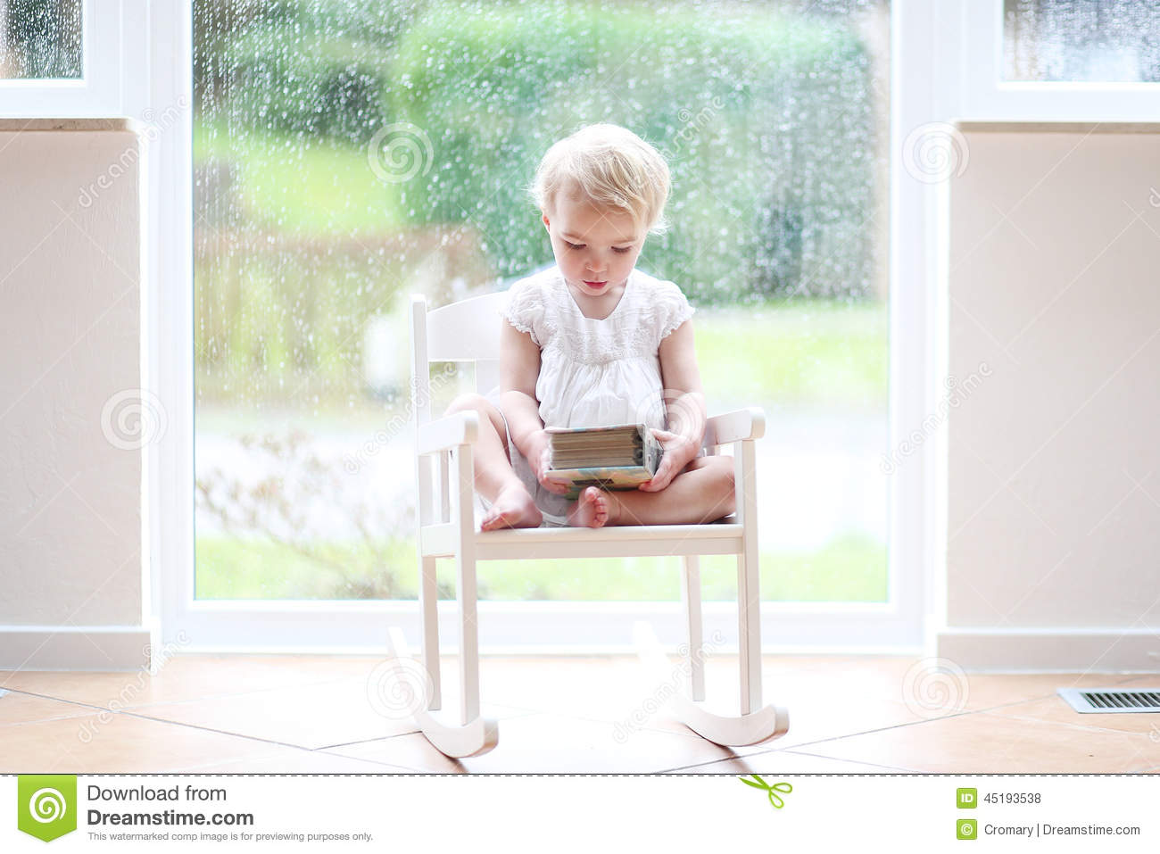 Little girl reading in front of big window stock photo for Toddler sitting chair