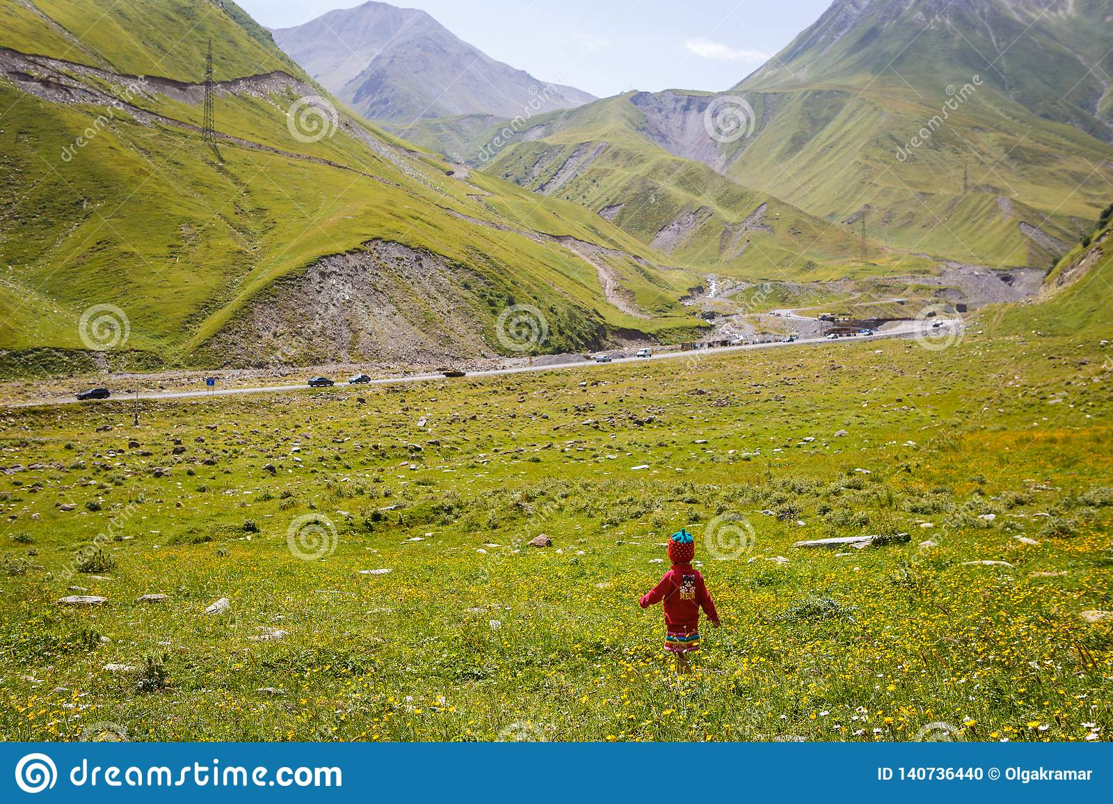A little girl in a red dress and a knitted cap-strawberry runs on a green field in the mountains.