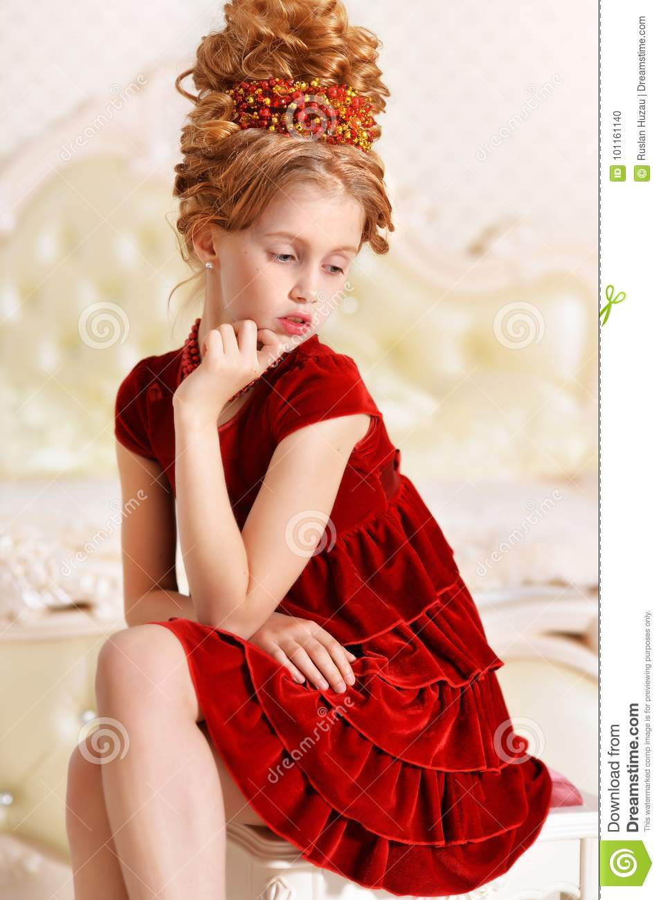 d148d738ff8a Emotional little girl in red velvet dress with retro hairstyle sitting on  beige couch