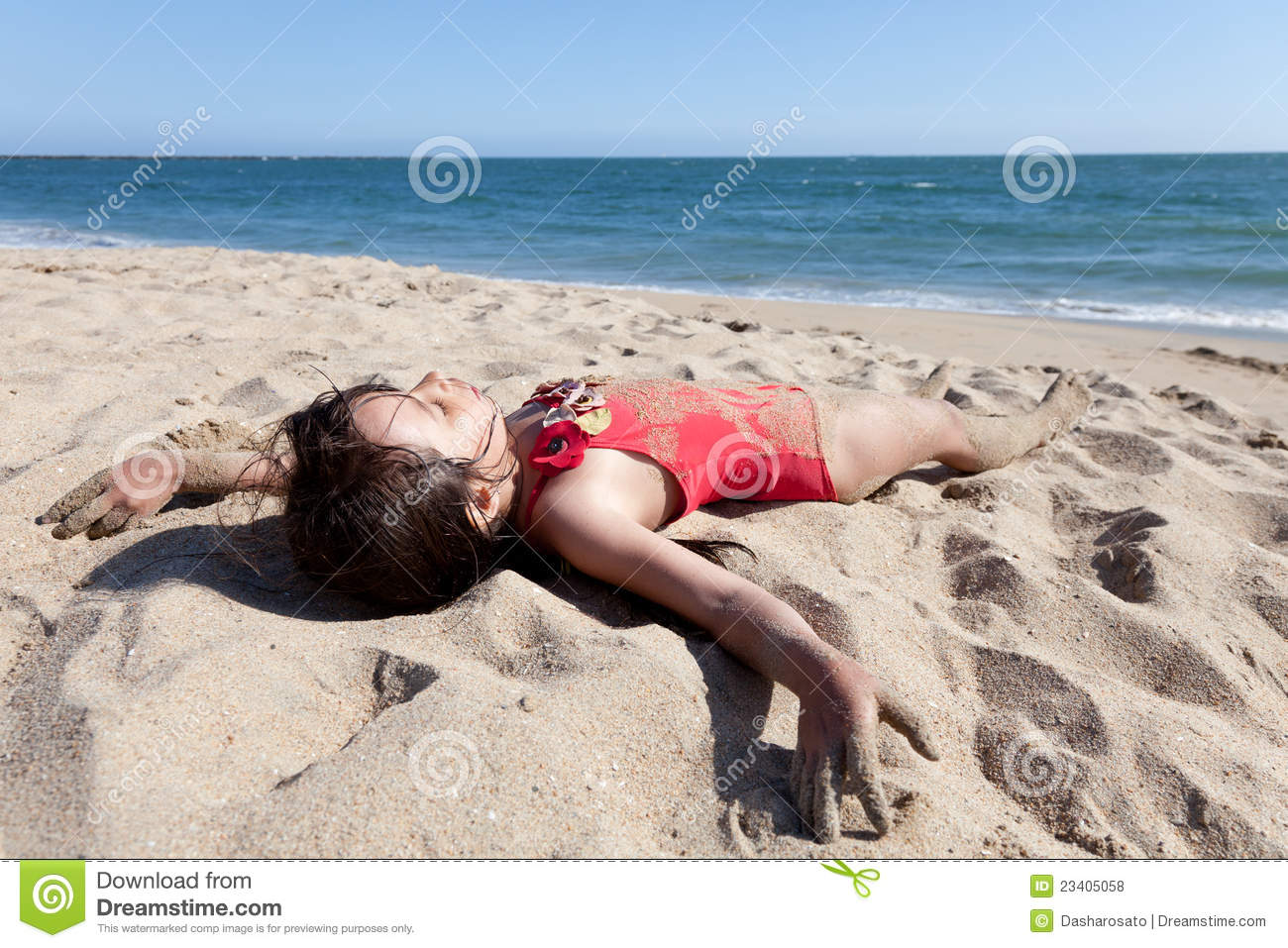 ... in red bathing suit on the beach with ocean and sky in the background