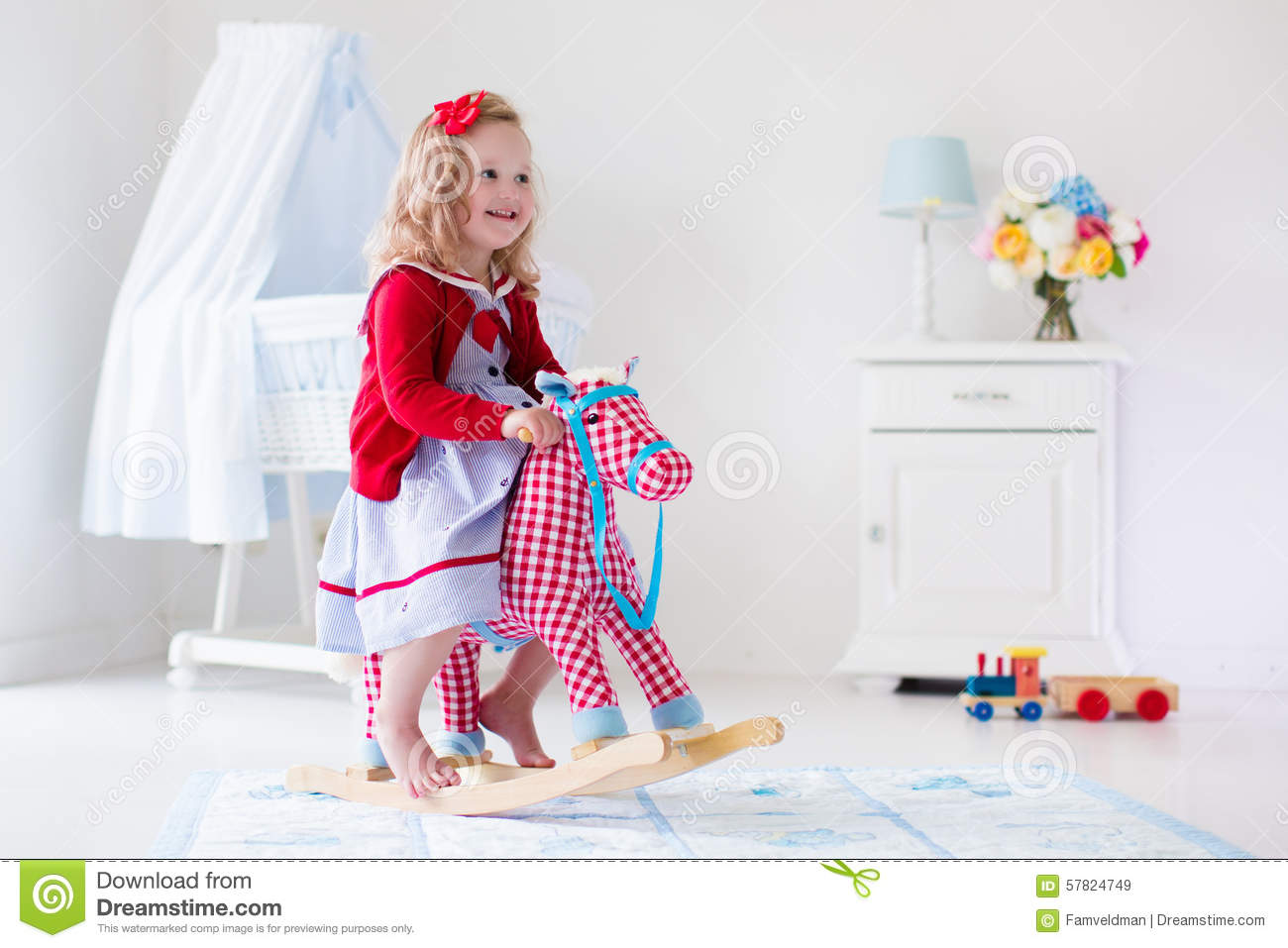 Little Girl Toys : Little girl riding a toy horse stock image