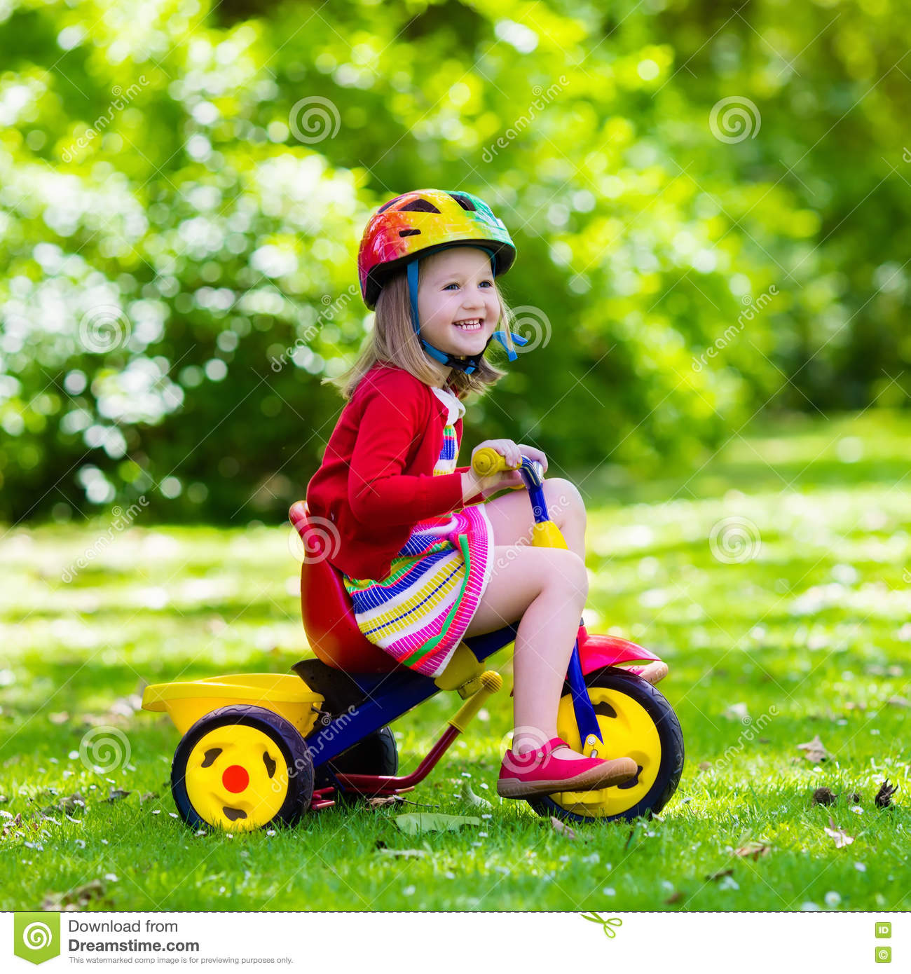 696a9baaec4 Cute girl wearing safety helmet riding her tricycle in sunny summer park.  Kids ride bicycle. First bike for little child. Active toddler kid playing  and ...