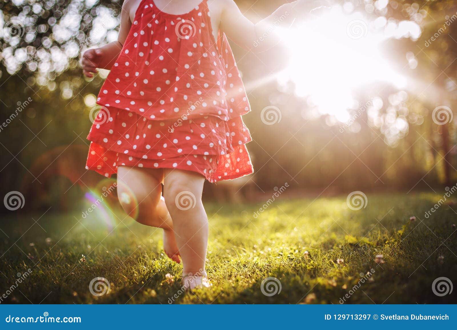 Little girl`s bare feet in the grass. little girl running