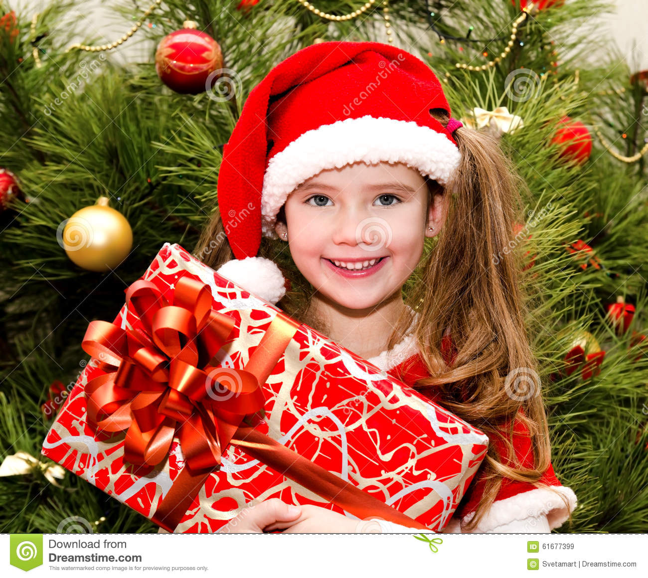 Little Girl Christmas Tree: Little Girl In Santa Hat With Gift Box Near Christmas Tree