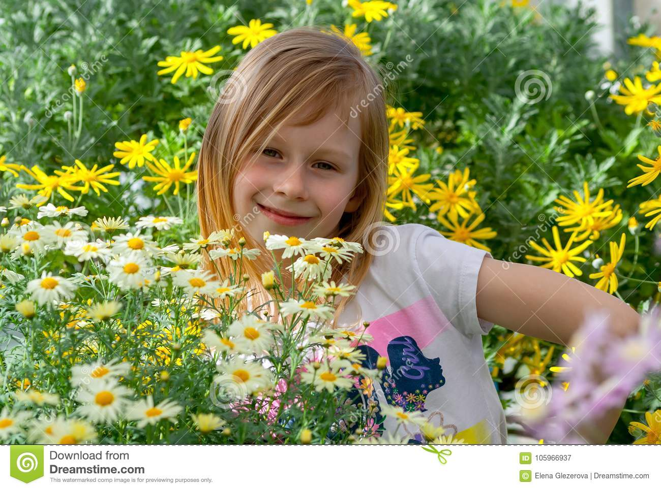 Little girl seven years old, surrounded by daisy flowers