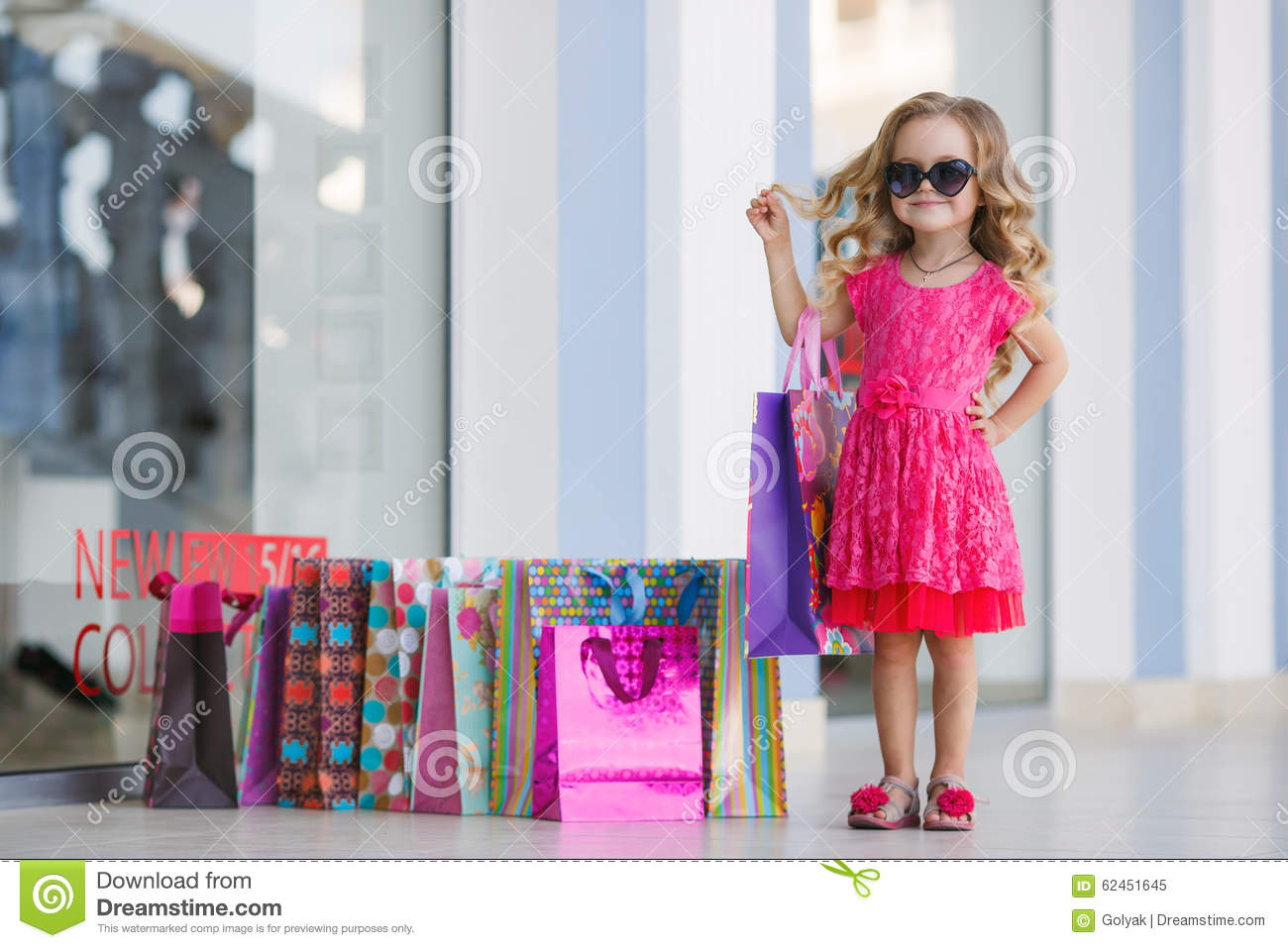 Little girl with shopping bags goes to the store stock for Nearby boutiques