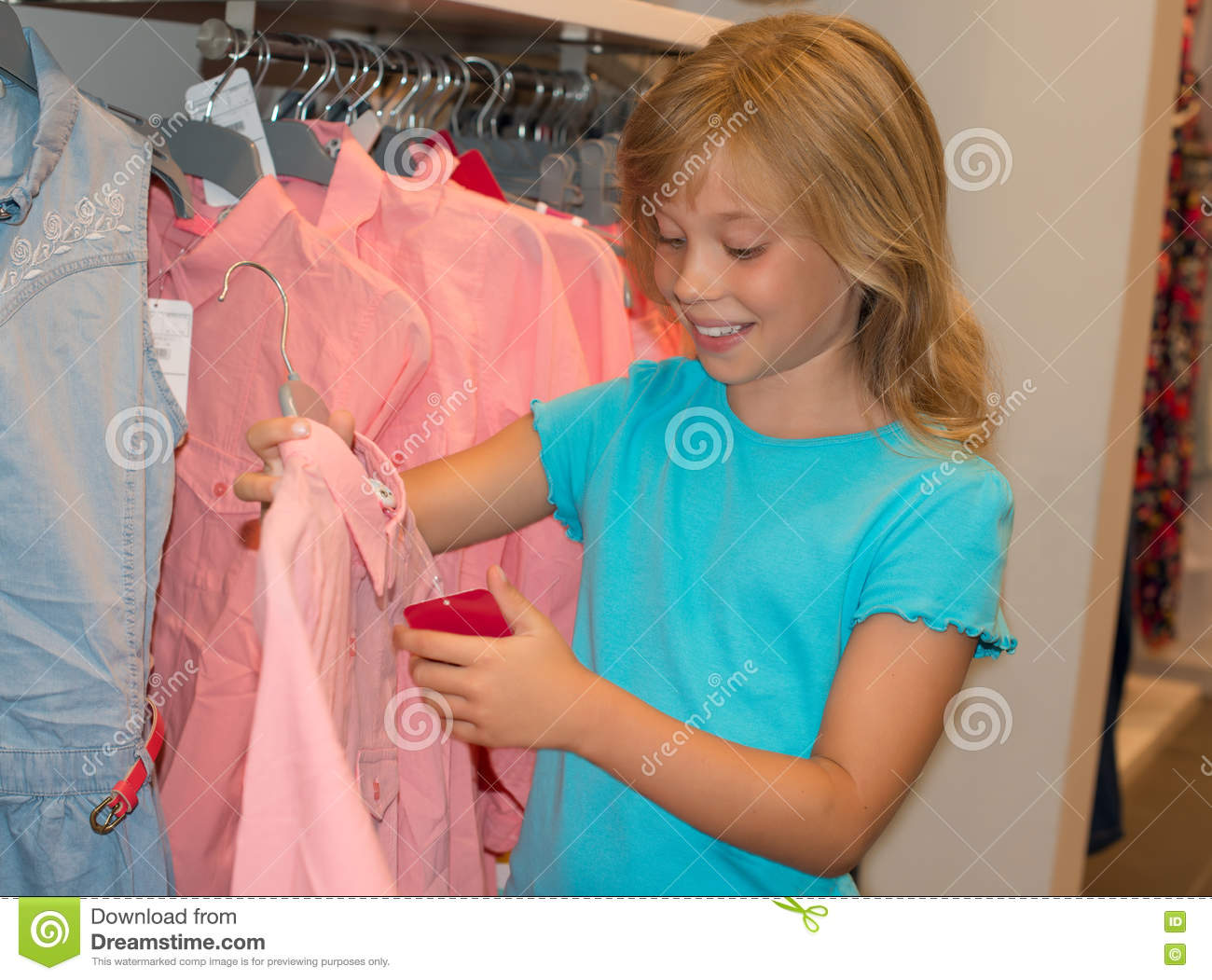 01393ebb2 Little girl shopping in clothes store. Child chooses dress at clothes shop.