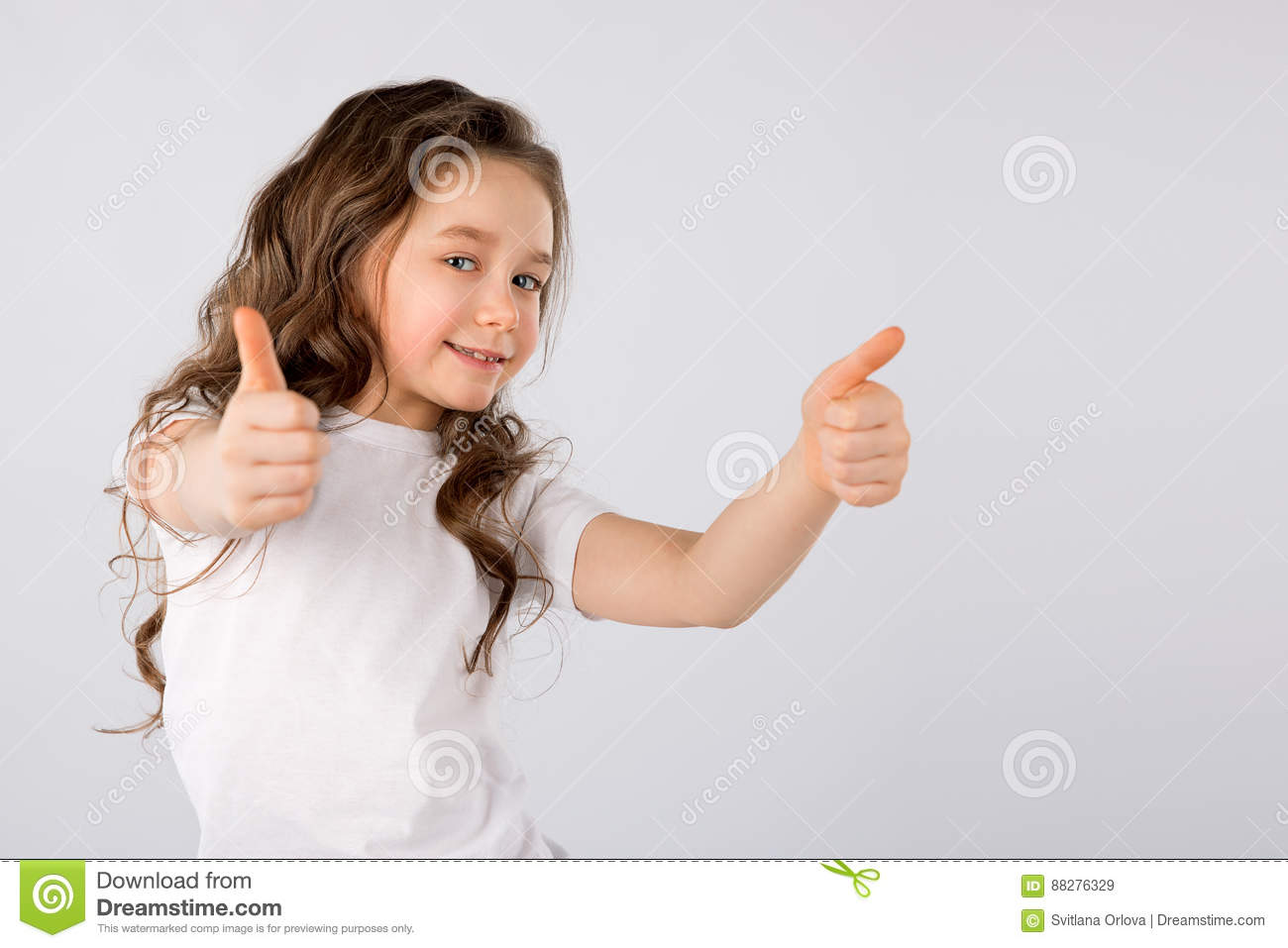 Little girl showing thumbs up gesture isolated on white background.