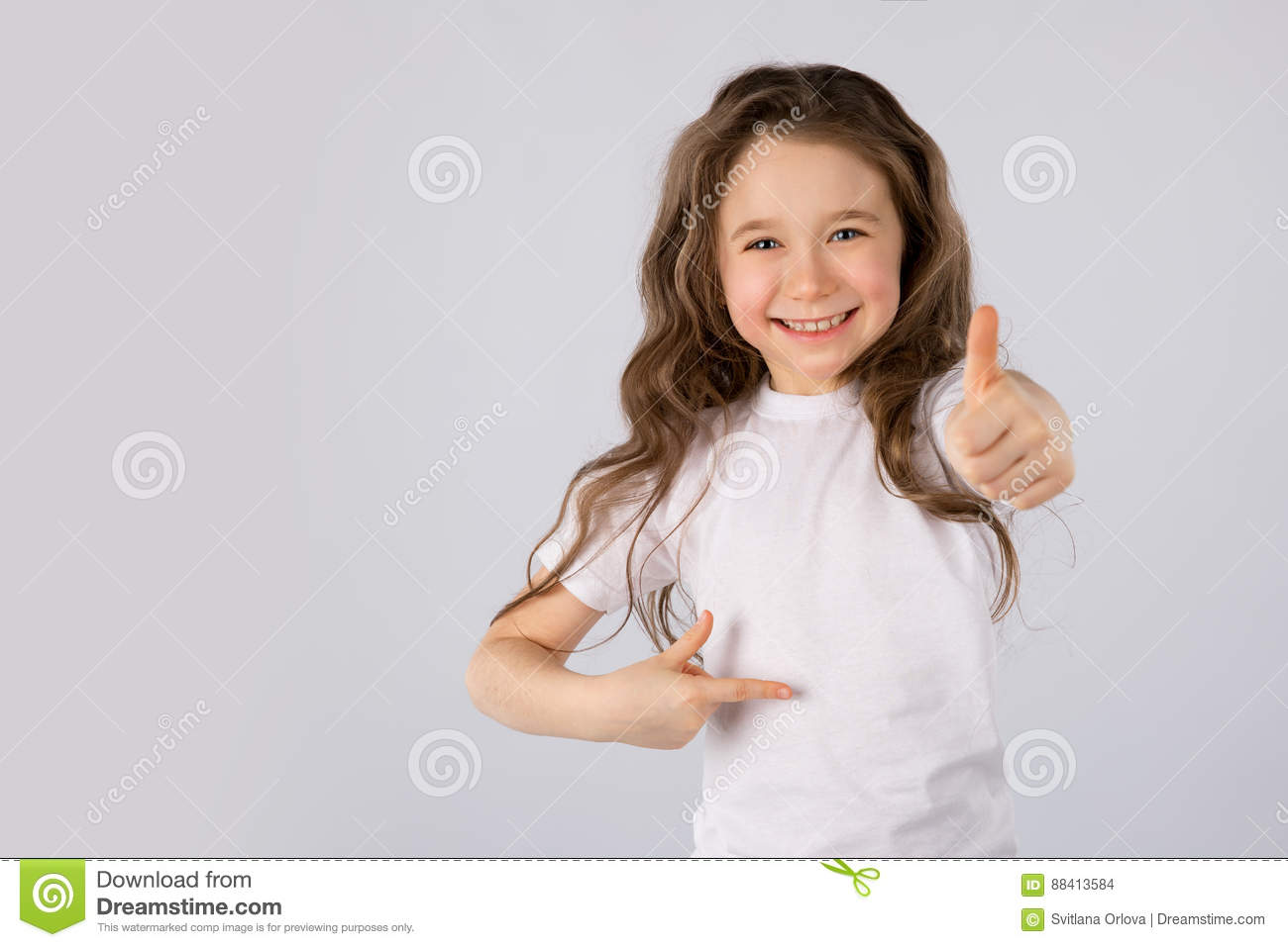 Little girl showing thumbs up gesture in a white T-shirt on white background.