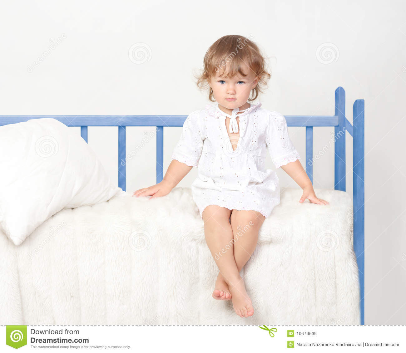 little girl sitting on the bed royalty free stock images