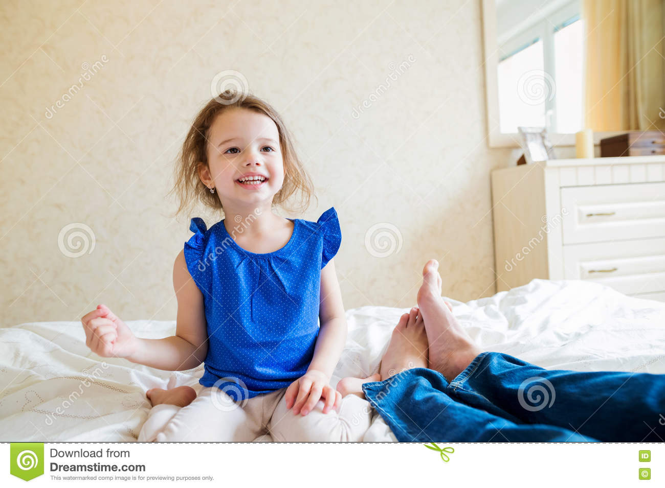 Happy Child Girl Is Sitting In The Bed Barefoot Royalty