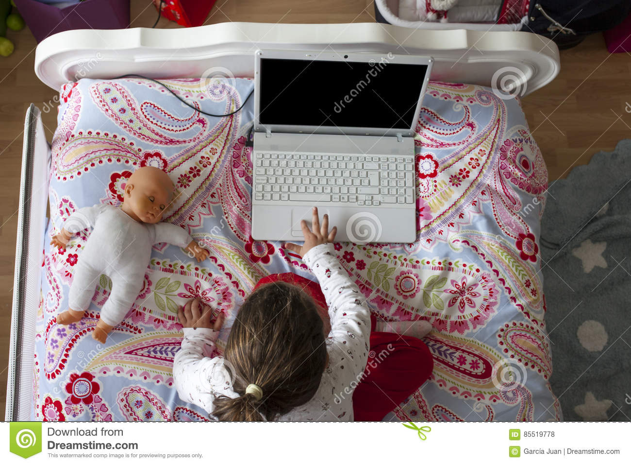 Little Girl Sitting In Bed And Playing Online Games Stock