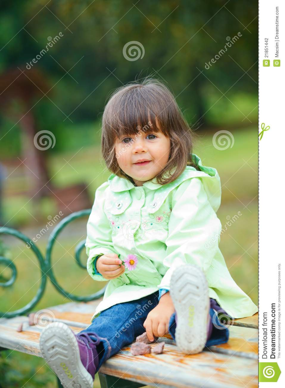 Little Girl Sitting On A Bench In The Park Stock
