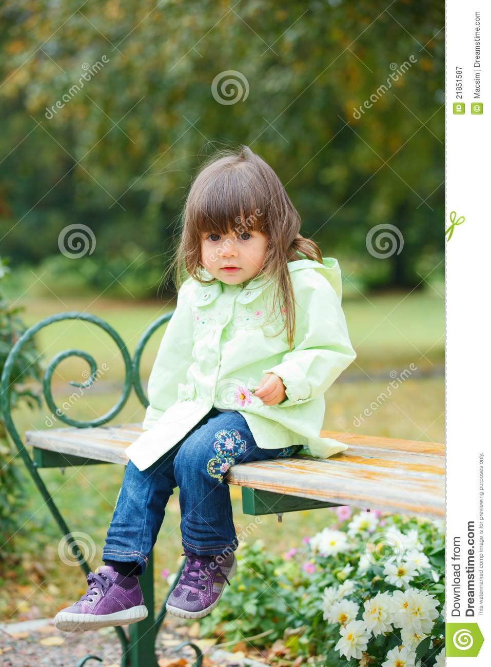 Little Girl Sitting On A Bench In The Park Royalty Free