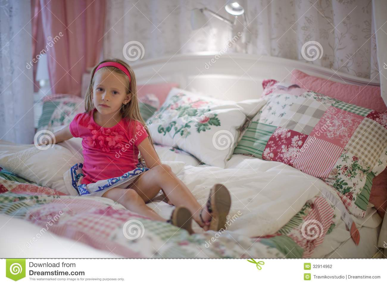 Little Girl Sitting In A Big Colorful Bed Stock Photo