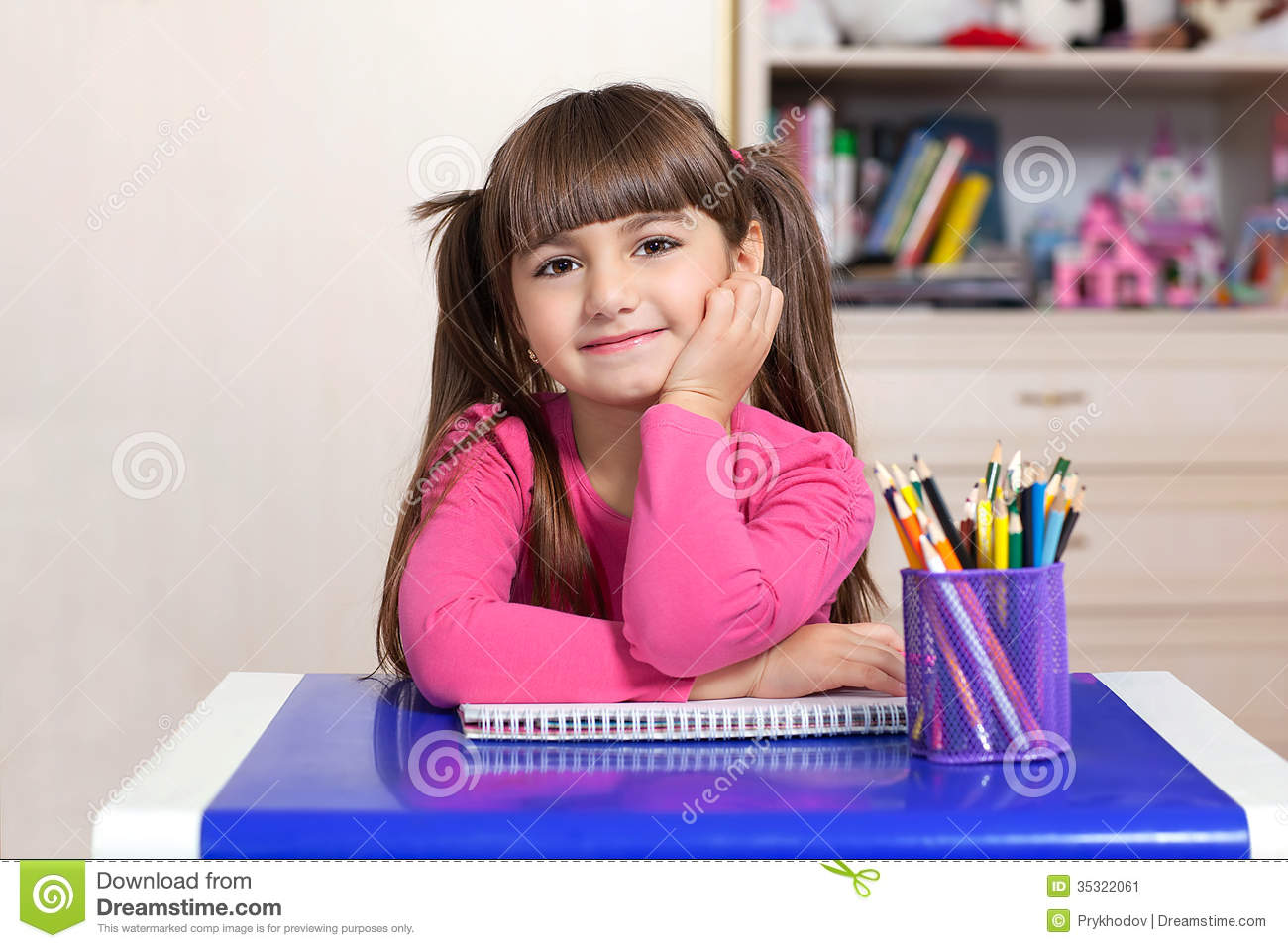 Little girl sitting in the children room at the table with color