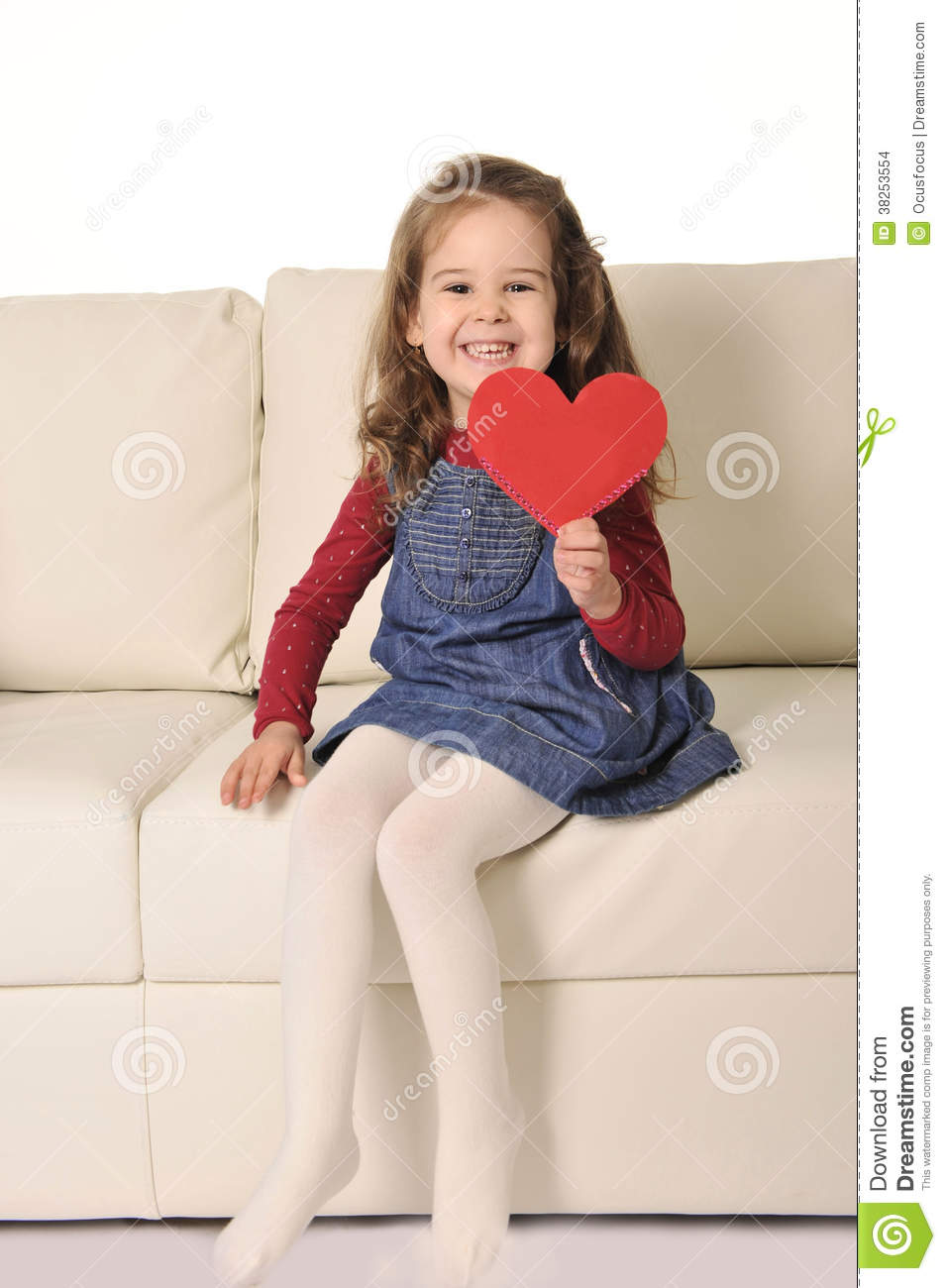 Little Girl Sitting On Couch Holding Red Heart Shape