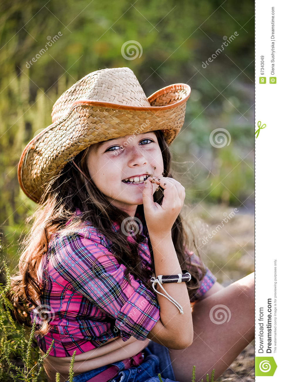 7f9af0704c567 Little Girl Sitting In A Field Wearing A Cowboy Hat Stock Image ...