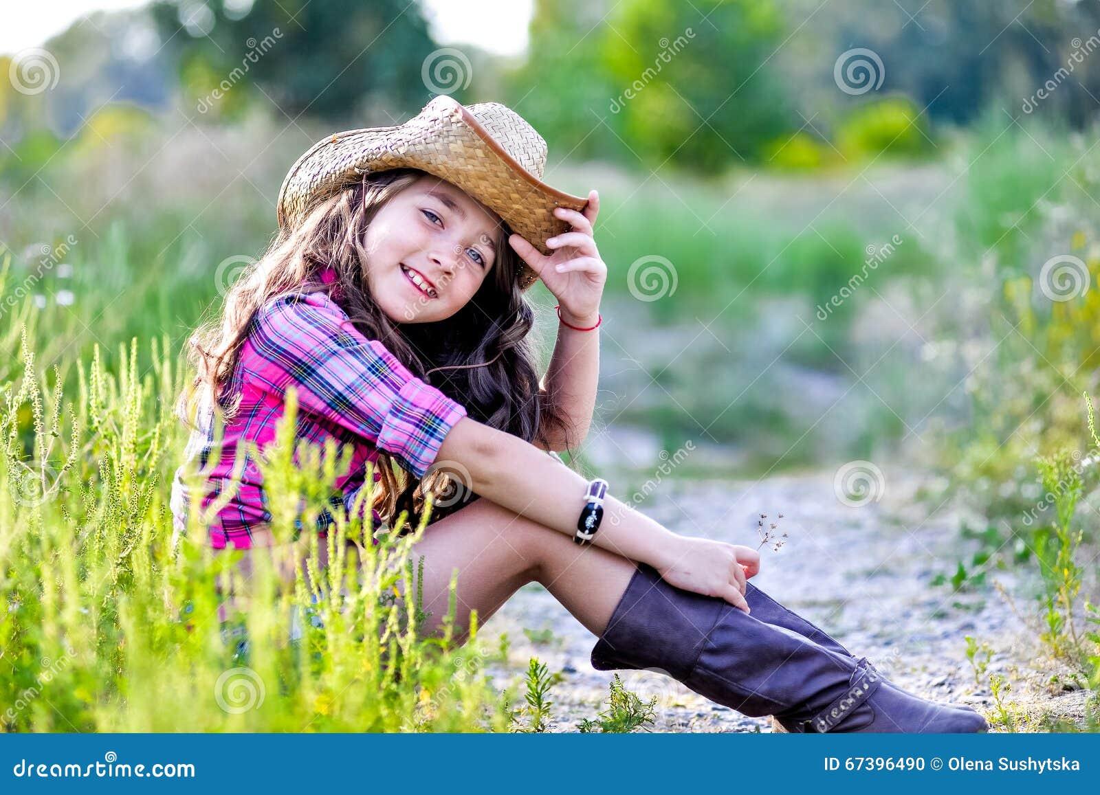 0b465f322b4ac Little Girl Sitting In A Field Wearing A Cowboy Hat Stock Photo ...