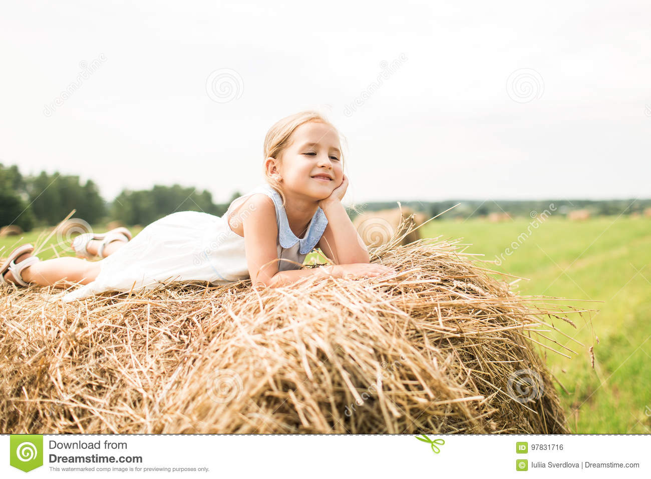 Little girl is sitting on a haystack, a summer concept