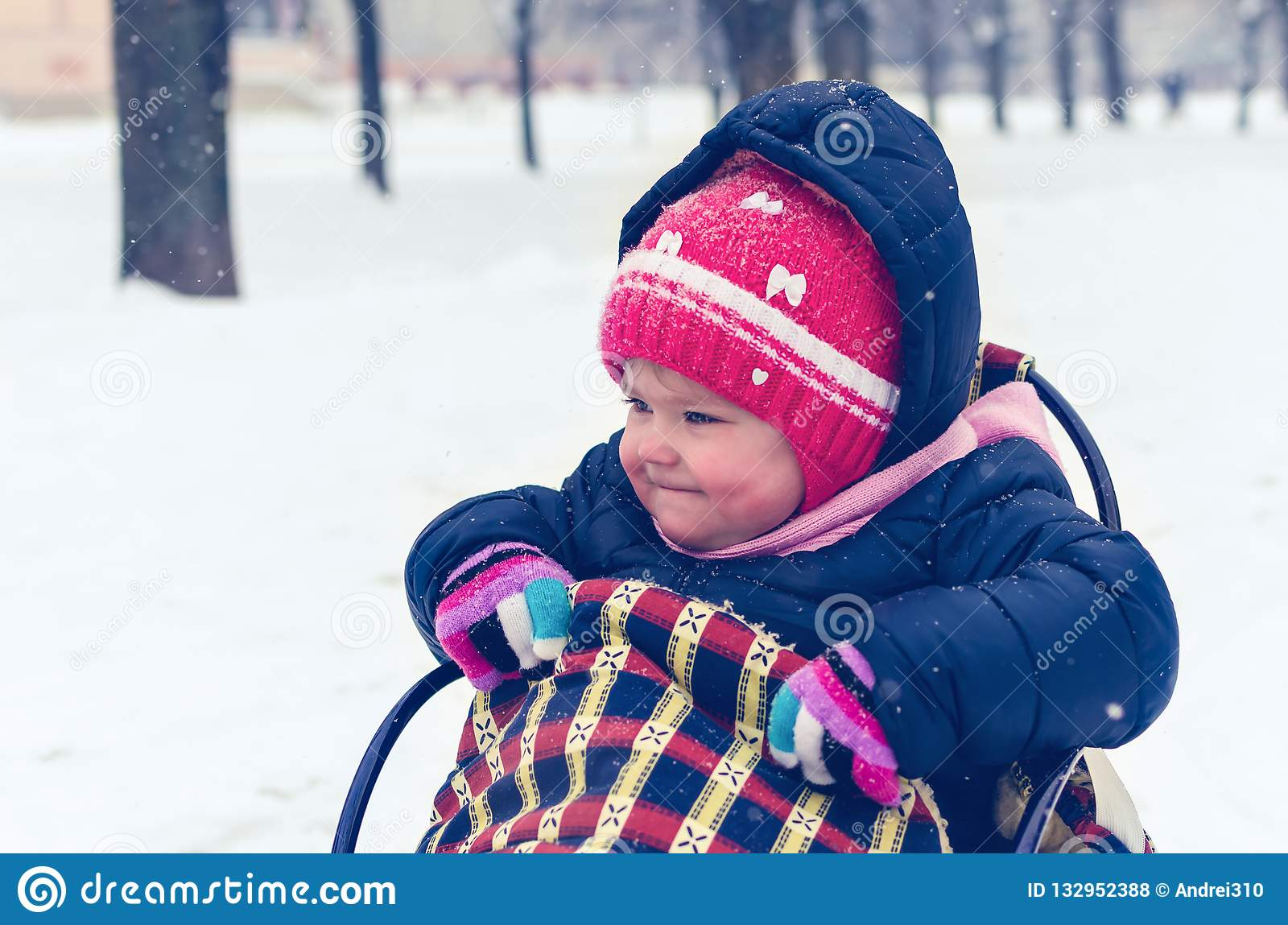 Little girl sitting on her sled in winter day