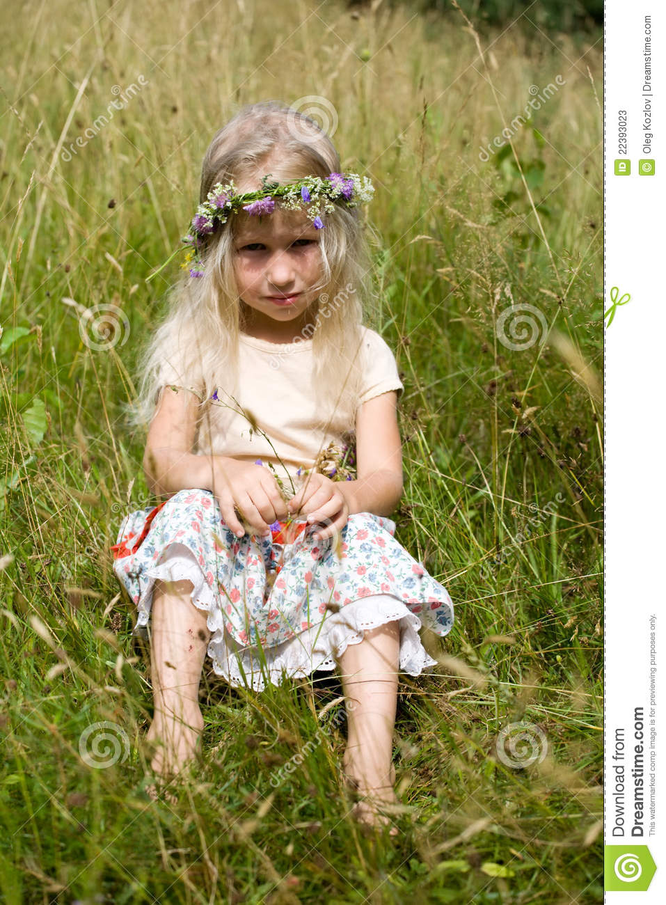 Little girl sitting at the meadow