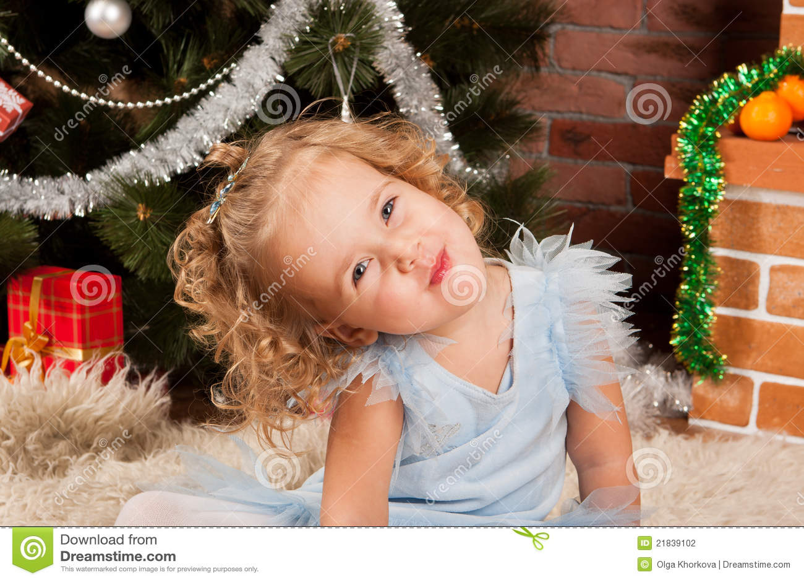 Little Girl Sitting Near Christmas Tree Stock Photo