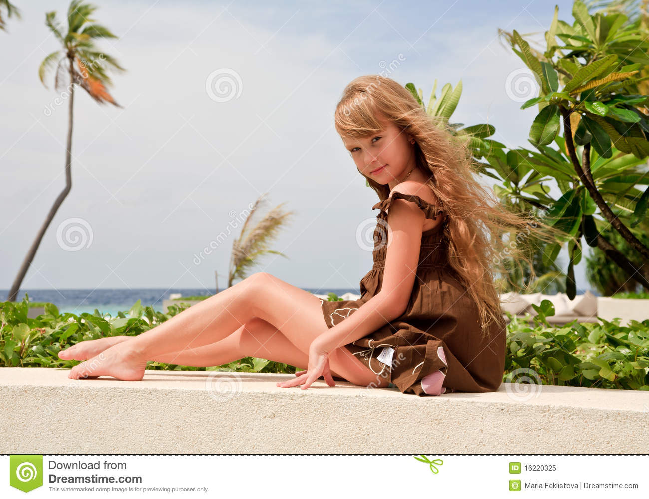 Royalty Free Stock Photo: Little girl sitting near ocean