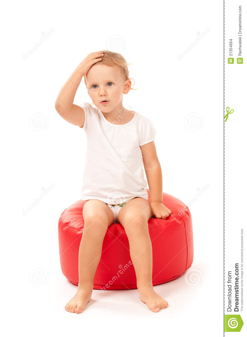 Little Girl Sitting On A Red Pouf Stock Photo