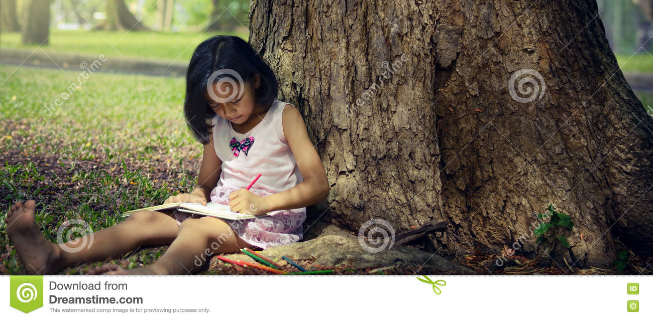 Little girl sitting under a big tree and writing a book.