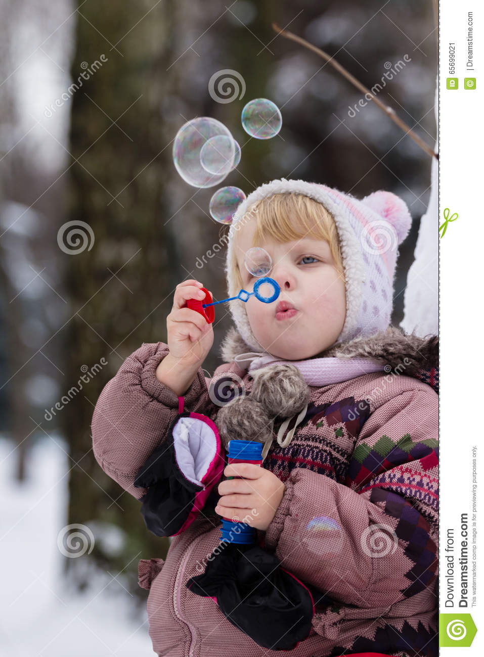 Little girl with soap bubles in winter