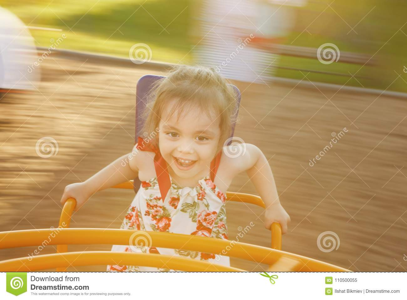 Little girl spinning on a children`s carousel among the playground.