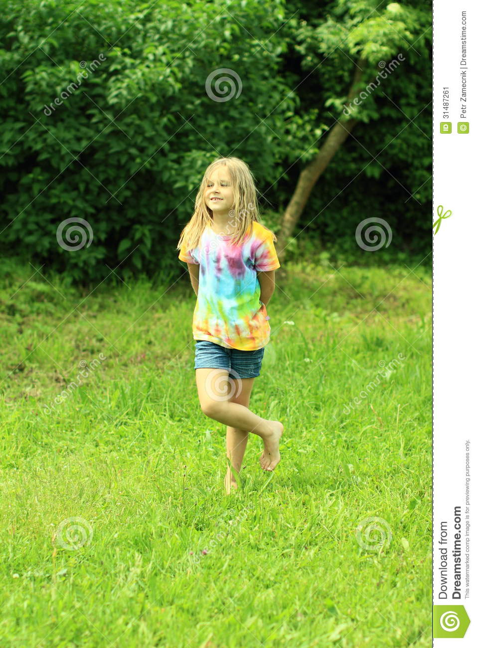 Little Girl Standing Barefooted On Grass Stock Image