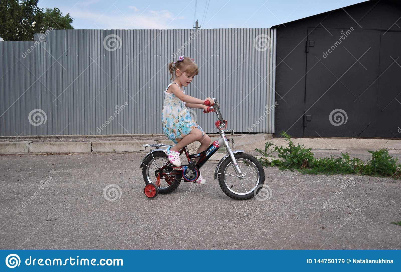 Little girl about five years old learn to ride a bike