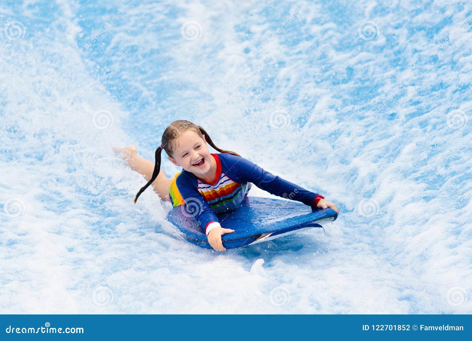 Little girl surfing in beach wave simulator