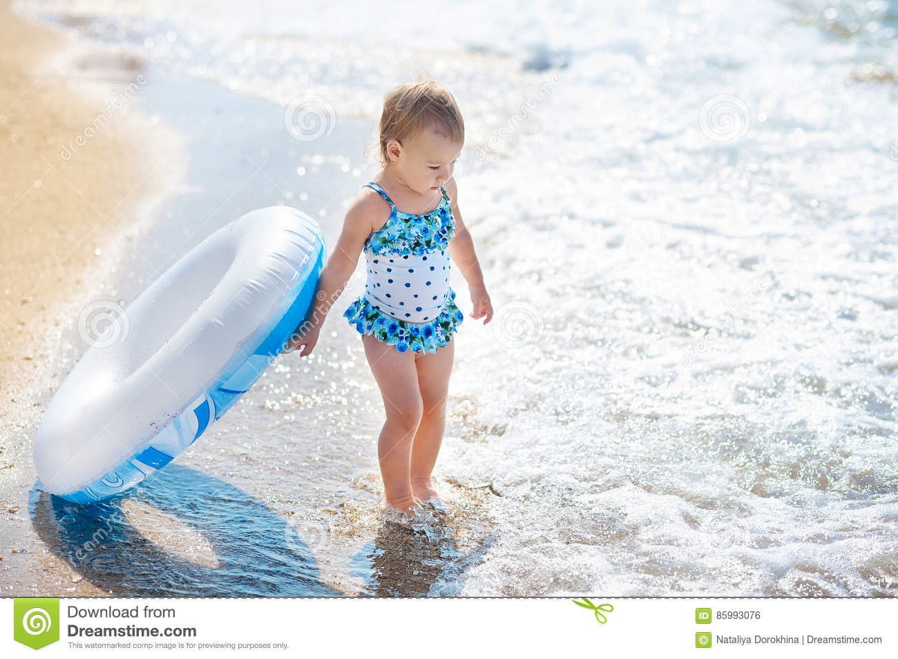 a46e42ee4431 Little girl in swim suit with swimming circle ready to go into the sea at  early sunset. Summer fun.