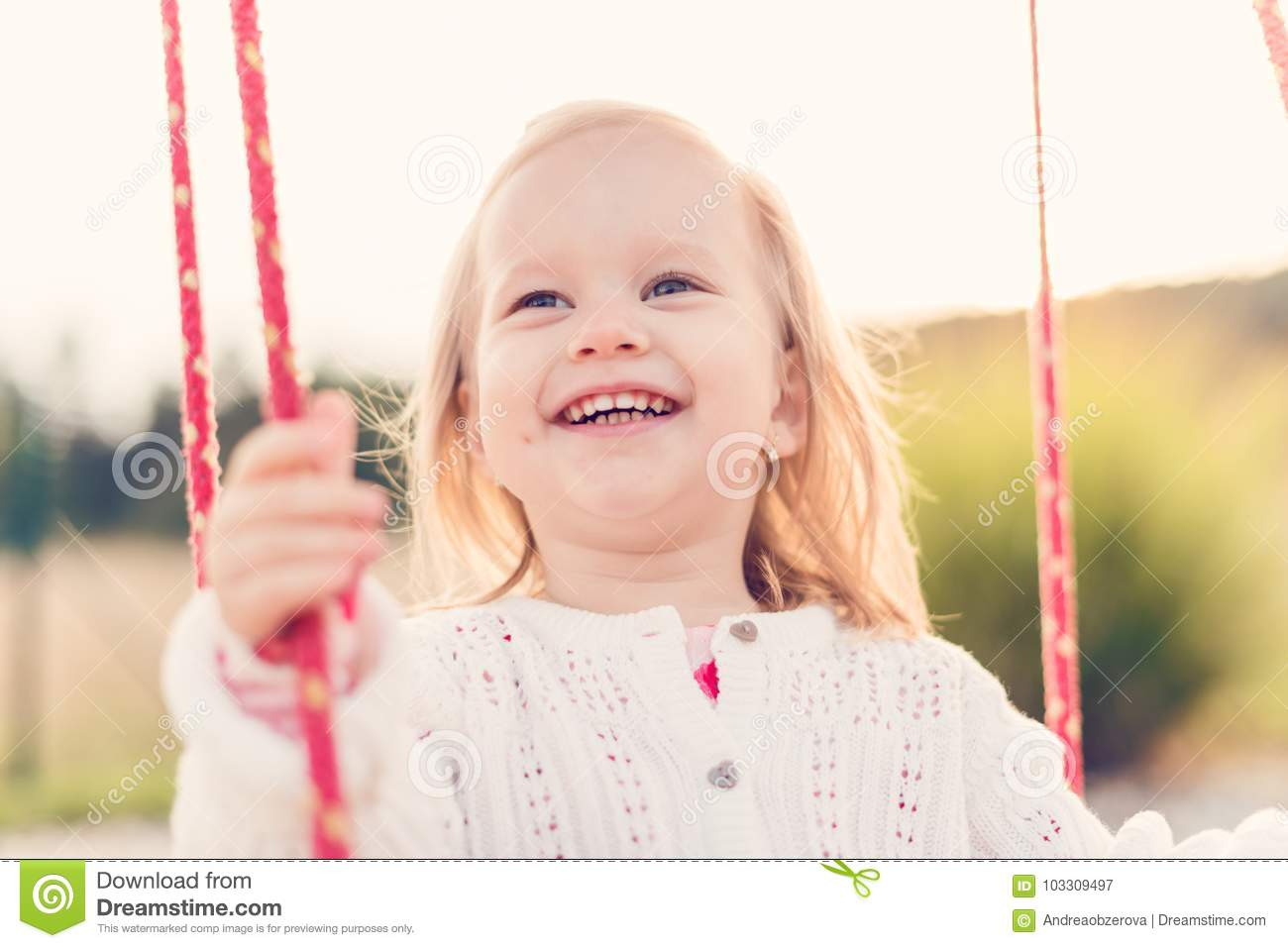 Little girl swinging on a playground. Childhood, Happy, Summer Outdoor Concept